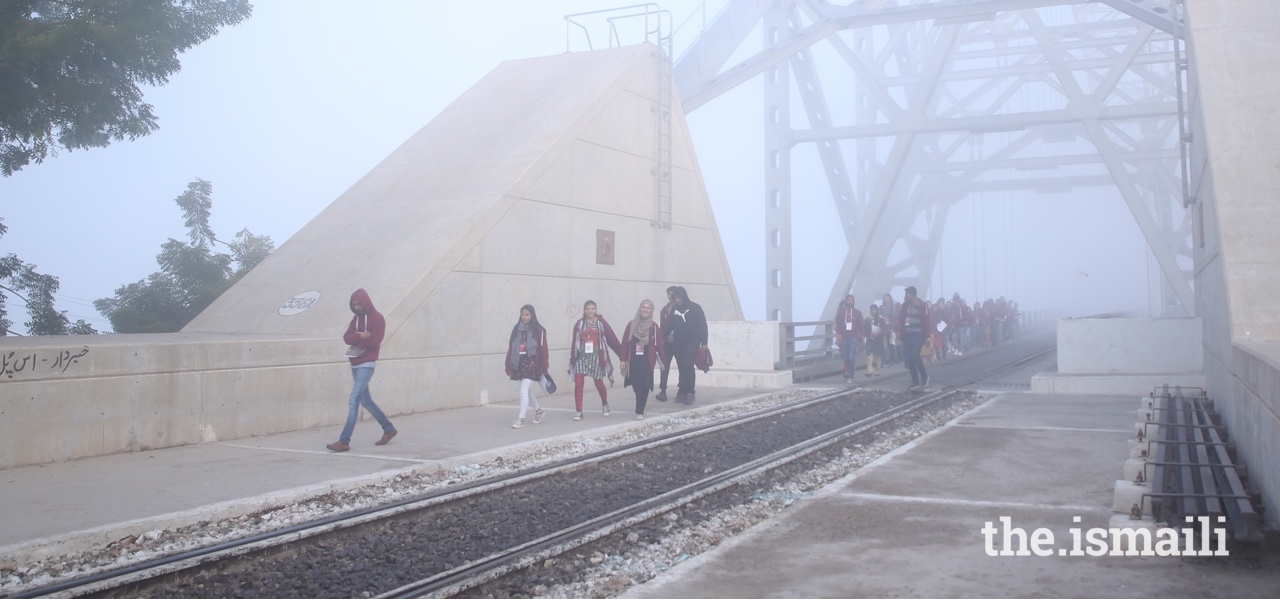 On a misty morning, HDT participants walk across the Sukkur bridge.
