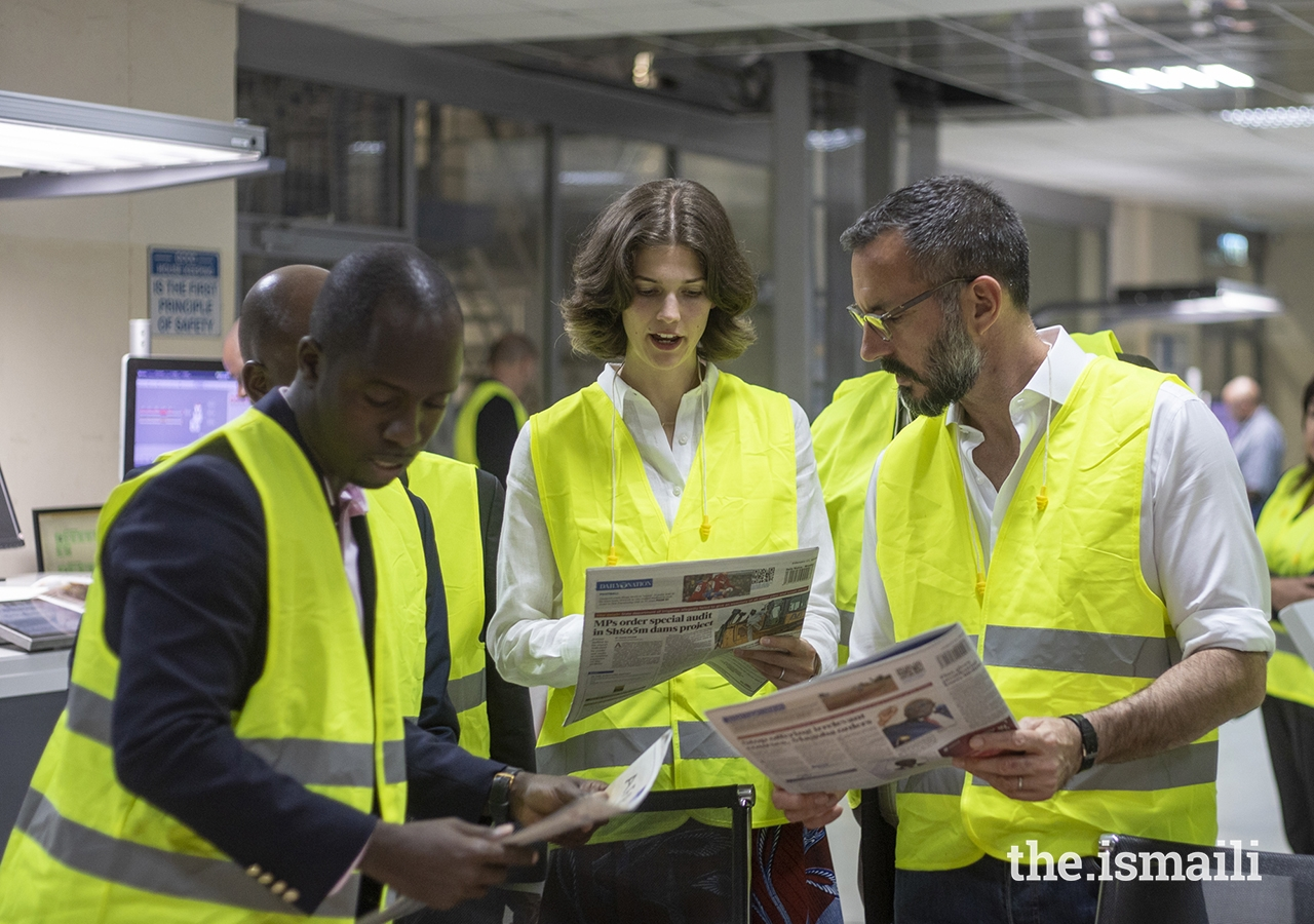 Nation Media Group's Head of Corporate Affairs, Mr. Clifford Machoka shows Prince Rahim and Princess Salwa newly printed copies of the Daily Nation newspaper, during their tour of the printing press.
