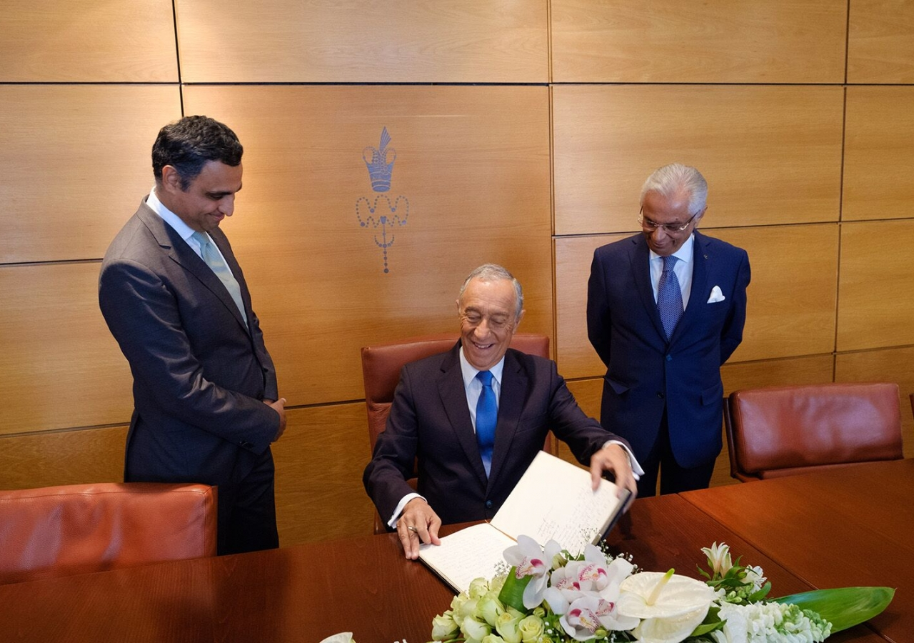 President Marcelo Rebelo de Sousa signs the visitor's book at the Ismaili Centre, Lisbon, with Ismaili Council President Rahim Firozali and Ismaili Imamat Diplomatic Representative Nazim Ahmad looking on.