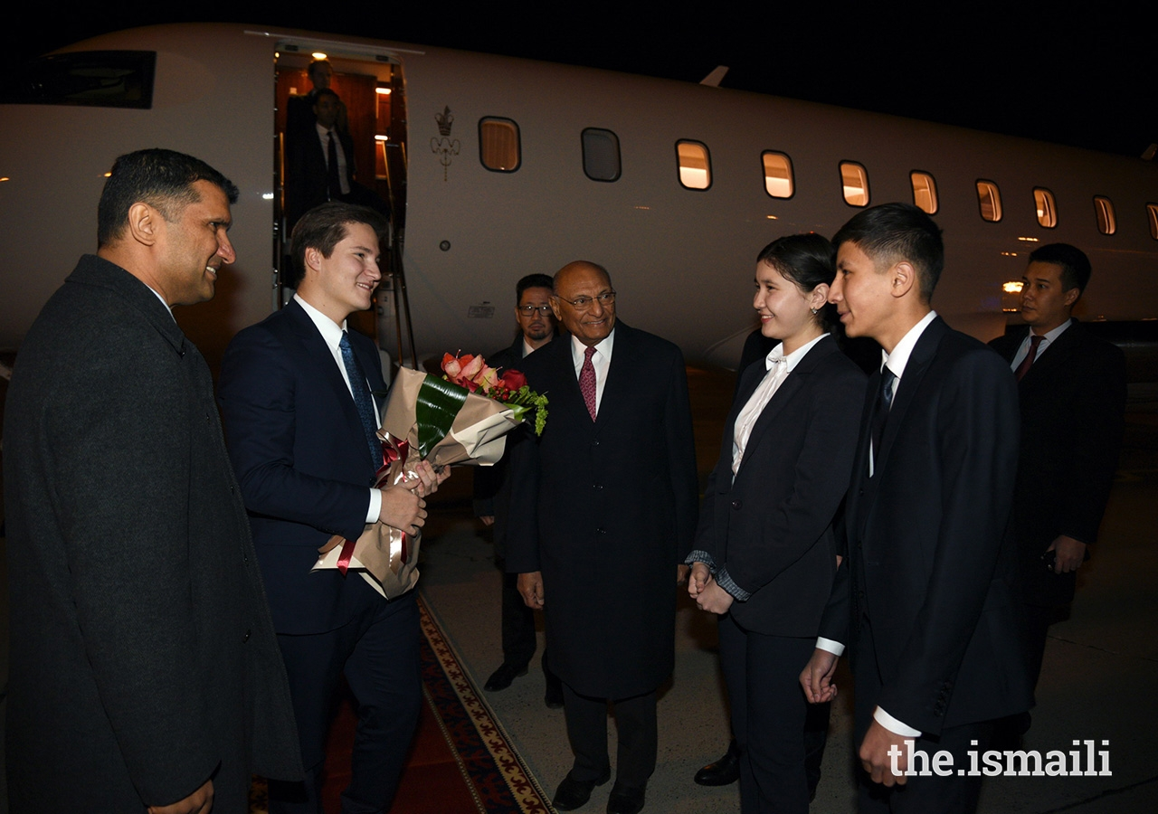 Prince Aly Muhammad is presented flowers by two students from the Aga Khan School in Osh upon his arrival in Kyrgyzstan.
