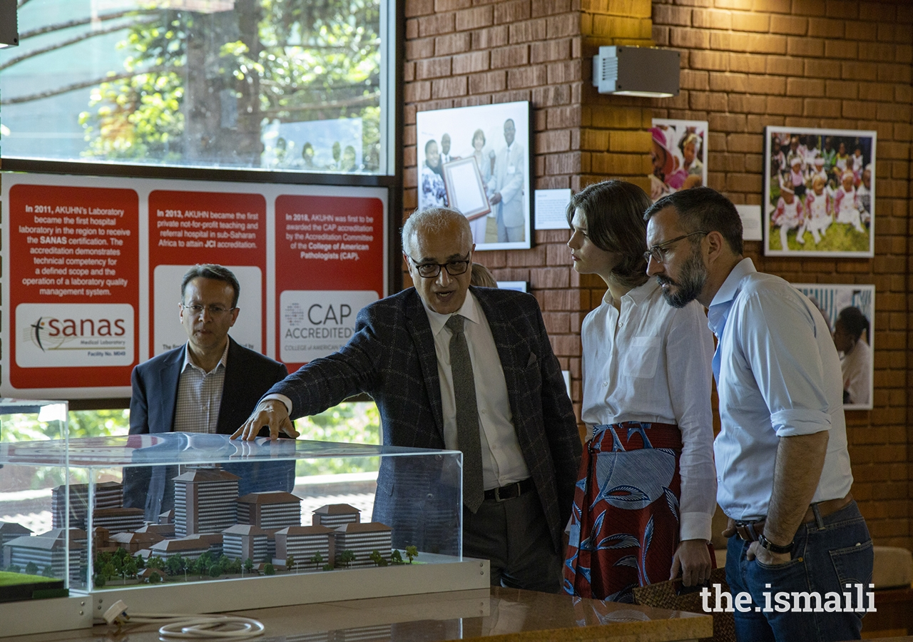 Mr Shawn Bolouki, CEO of the Aga Khan University Hospital in Nairobi, Kenya uses an architectural model to describe key features of the Aga Khan University Centre, currently under construction, to Prince Rahim and Princess Salwa. In the background are images of a specially curated photography exhibition on the history of the hospital, launched in July 2019 to commemorate the 60th Anniversary of AKUH Nairobi.