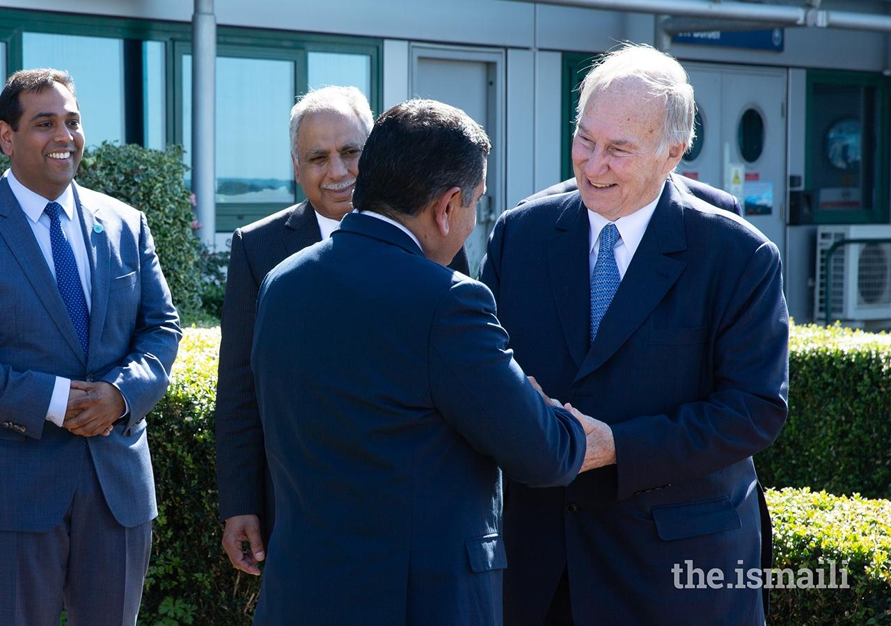 Mawlana Hazar Imam bids farewell to Lord Ahmad of Wimbledon, as President Liakat Hasham and Vice-President Farhad Mawani look on.