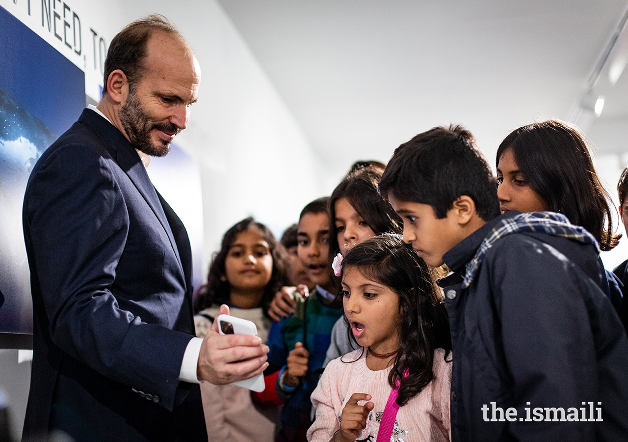 Prince Hussain interacts with young students at The Living Sea photo exhibition in Lisbon.