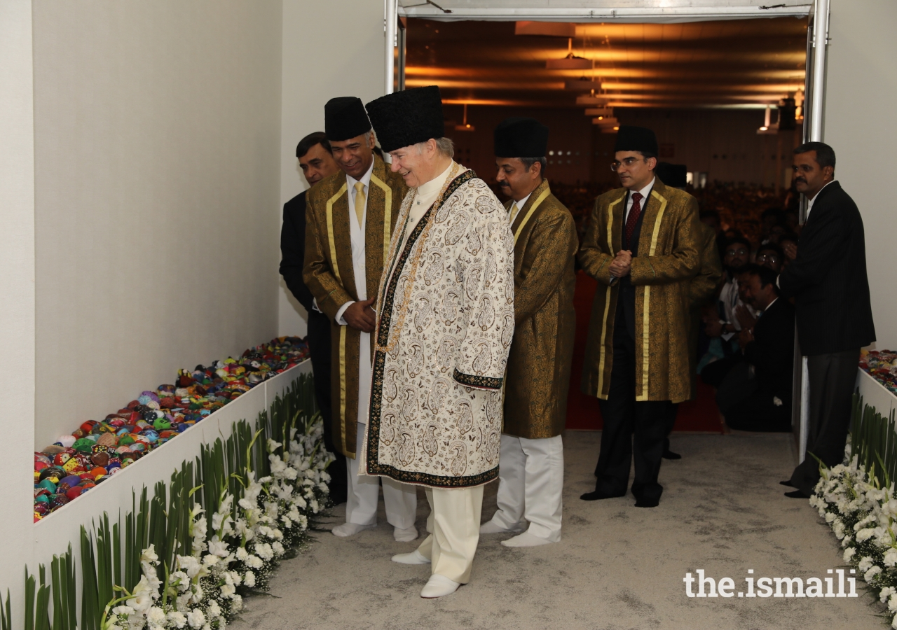 After exiting the Darbar hall, Mawlana Hazar Imam stops to observe artwork created by young students for the occasion of his Diamond Jubilee visit to India.