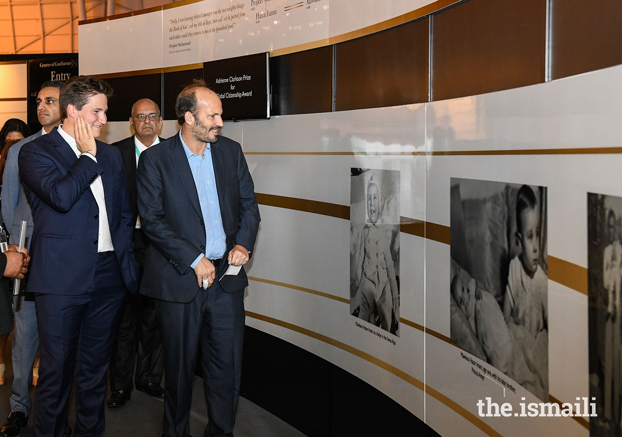 Prince Hussain and Prince Aly Muhammad admire a photograph of Mawlana Hazar Imam as a young boy, during their tour of the Rays of Light exhibition at the Diamond Jubilee Celebration in Lisbon.
