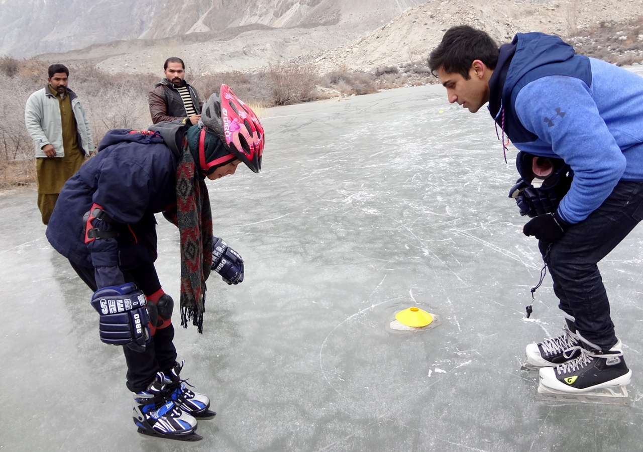 Ice hockey player Omar Kanji teaches a student to balance on ice skates in northern Pakistan.
