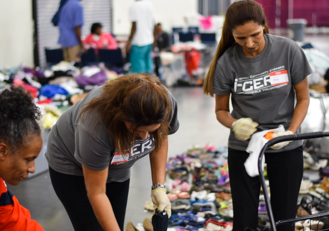 I-CERV volunteers organizing and bagging donated clothing items at the George R. Brown Convention Center.