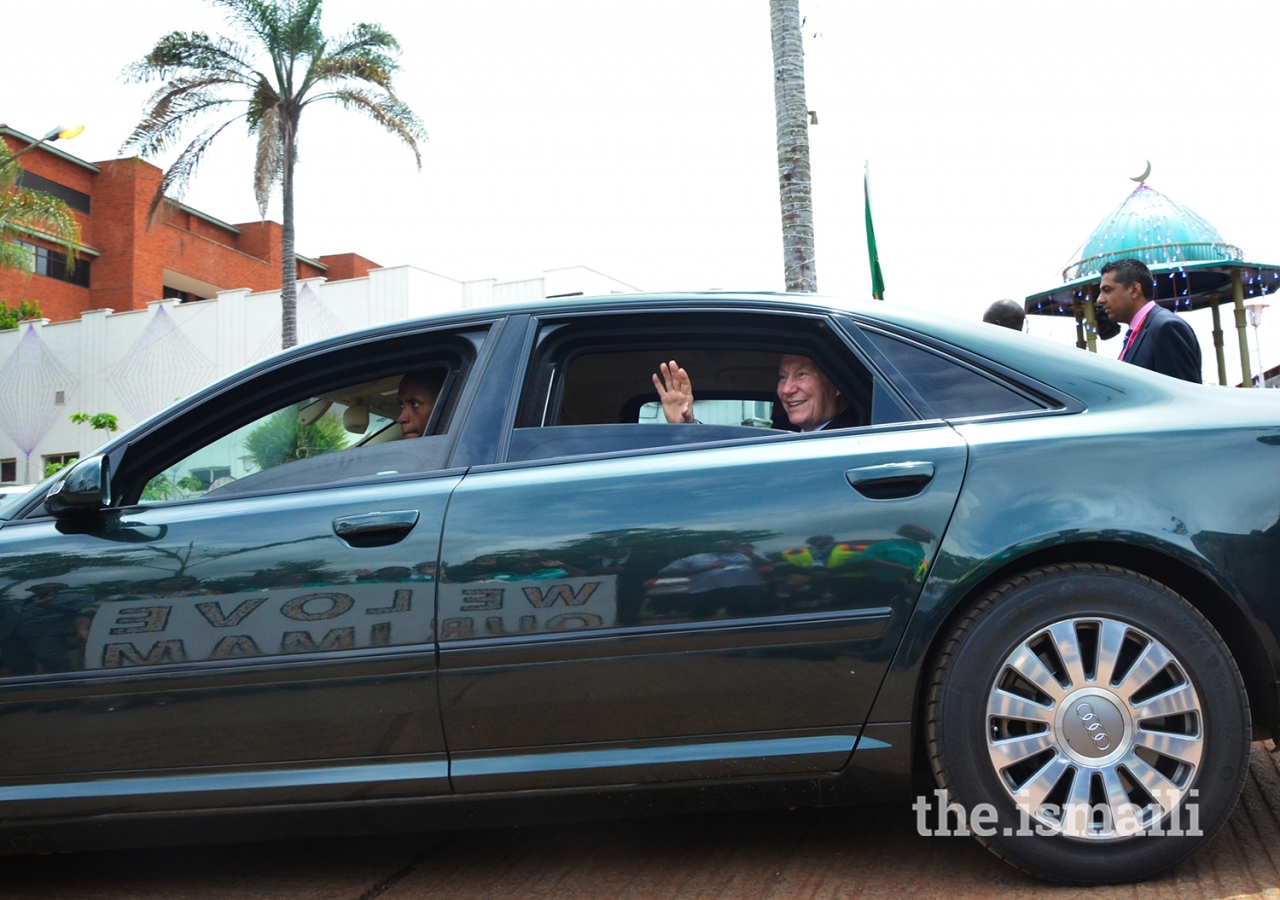 Mawlana Hazar Imam waves to young volunteers after departing the Darbar hall. A banner message created by pre-school children is reflected on the car.