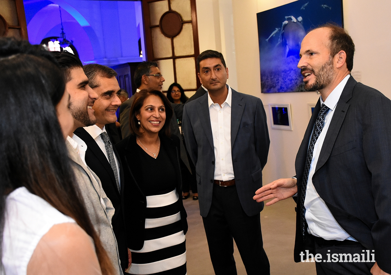 Prince Hussain in conversation with guests at an event hosted by the Aga Khan Council for Kenya, featuring an exhibition of his marine photography and cultural performances.