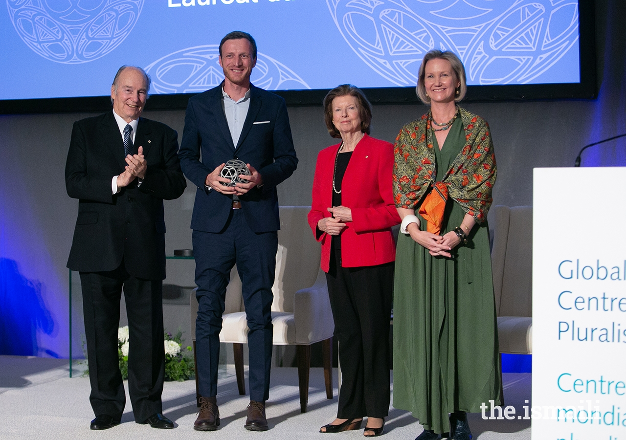 Igor Radulović, on behalf of the group Learning History that is not yet History, poses for a photo with Mawlana Hazar Imam, Global Centre for Pluralism Board Member Huguette Labelle, and Global Centre for Pluralism Secretary General Meredith Preston McGhie.