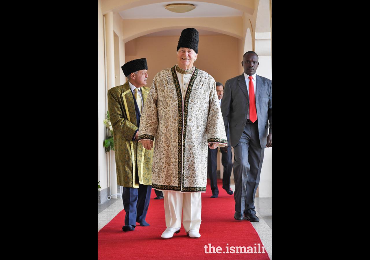 Mawlana Hazar Imam making his way to the Darbar hall to meet with the Ugandan Jamat, followed by President Minaz Jamal.