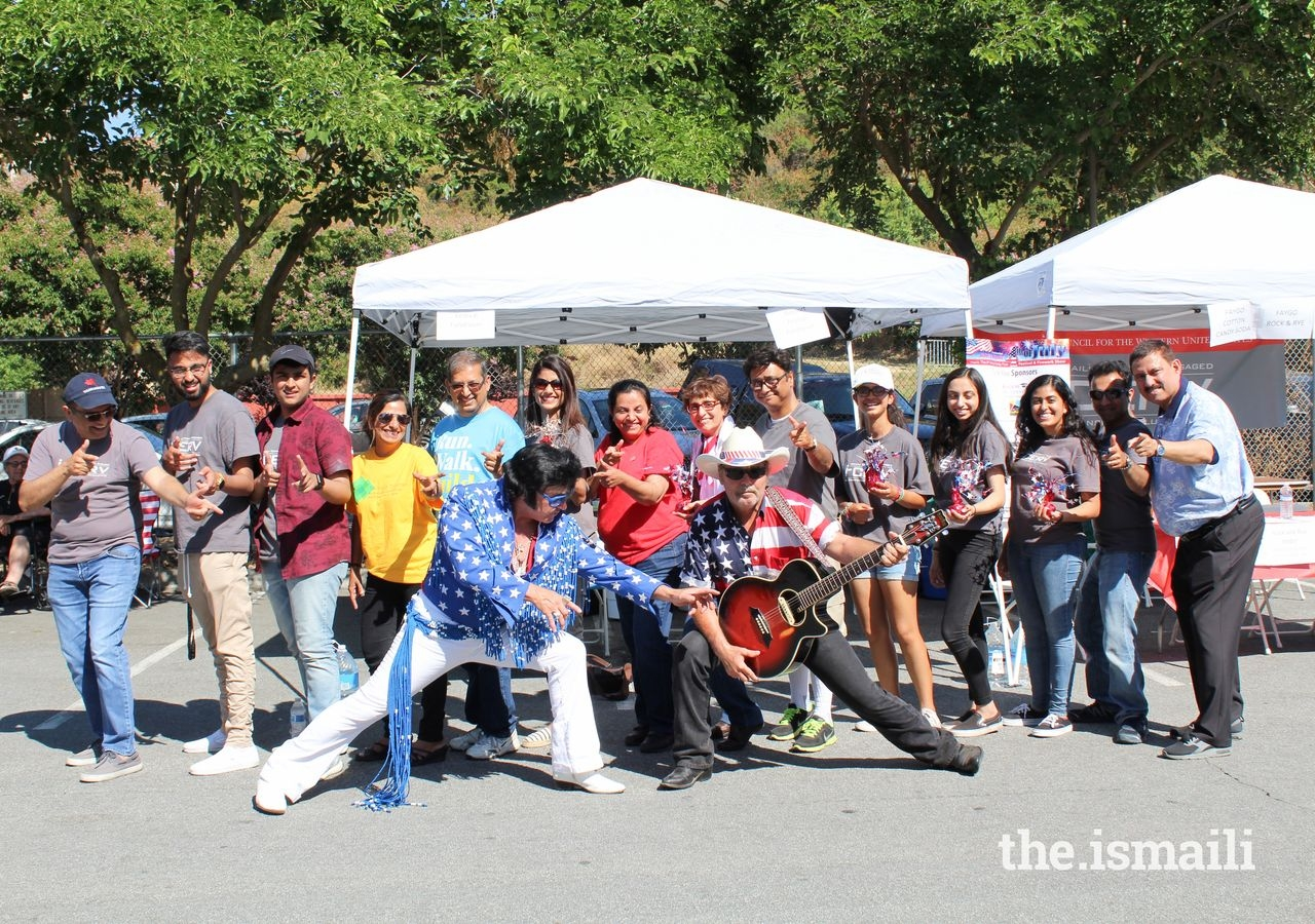 The northern California I-cerv team at San Jose's 4th of July event takes a picture with an Elvis impersonator and his guitarist.