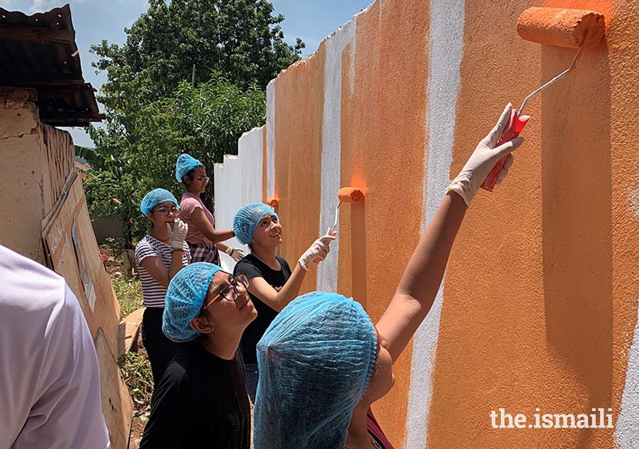 Young volunteers from Kampala work together to repaint the Kyanja Muslim Nursery School.