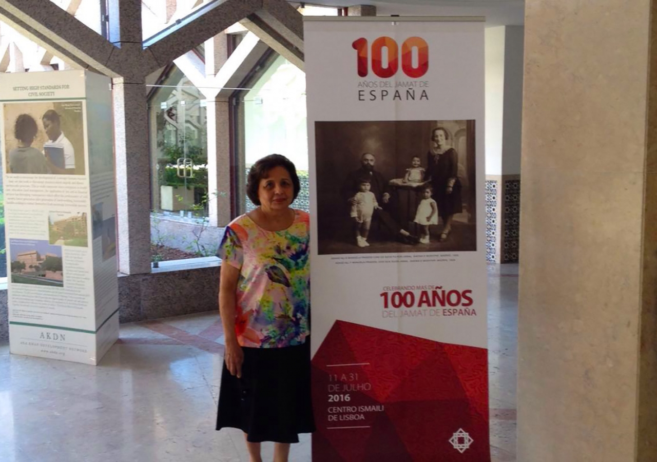 Mehrun Karim, granddaughter of Ashad Ali Haji, next to a banner for the exhibition. Ismaili Council for Portugal / Nadia Silva