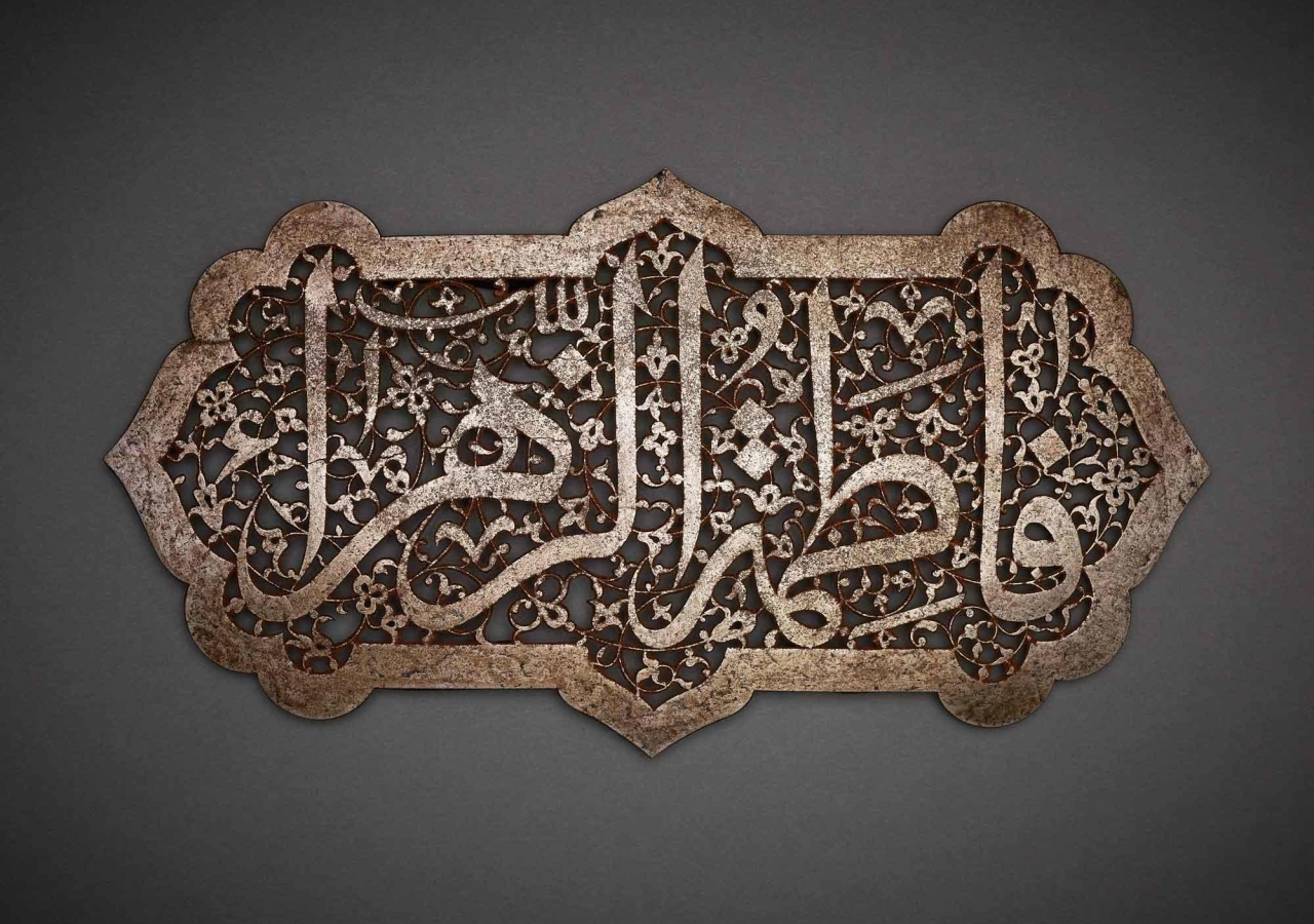 """The inscription Fatima al-Zahra' (""""Fatima the Radiant""""), the name of the Prophet's daughter and her epithet, is carved out in an elegant contrast between the solid lines of the magisterial thuluth script and the intricately carved floral spiral that forms its background."""