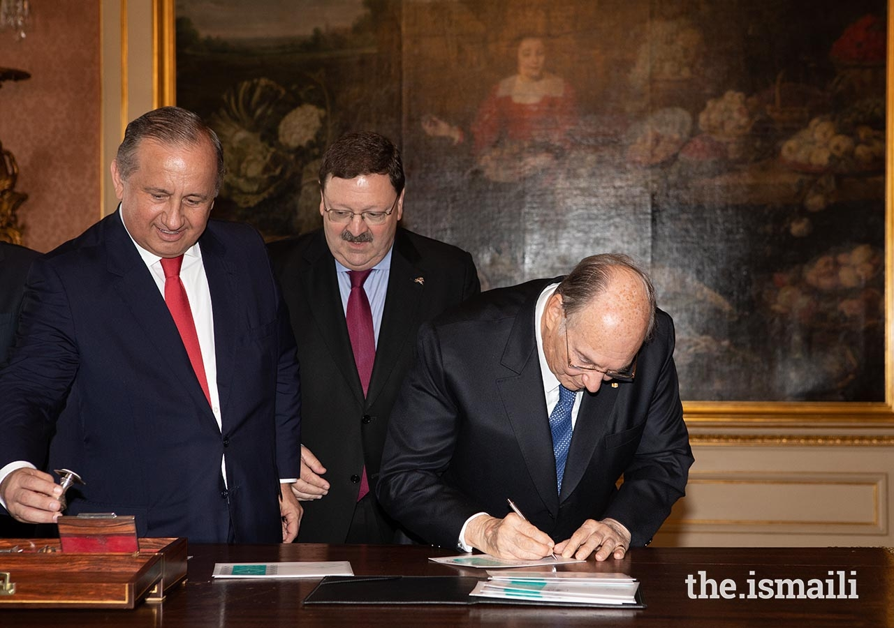 Mawlana Hazar Imam signs a special commemorative issue of the Diamond Jubilee postage stamp, as Francisco Lacerda, CEO of CTT (Portugal Postal Services), and Raul Moreira, Head of Philately for CTT, look on.