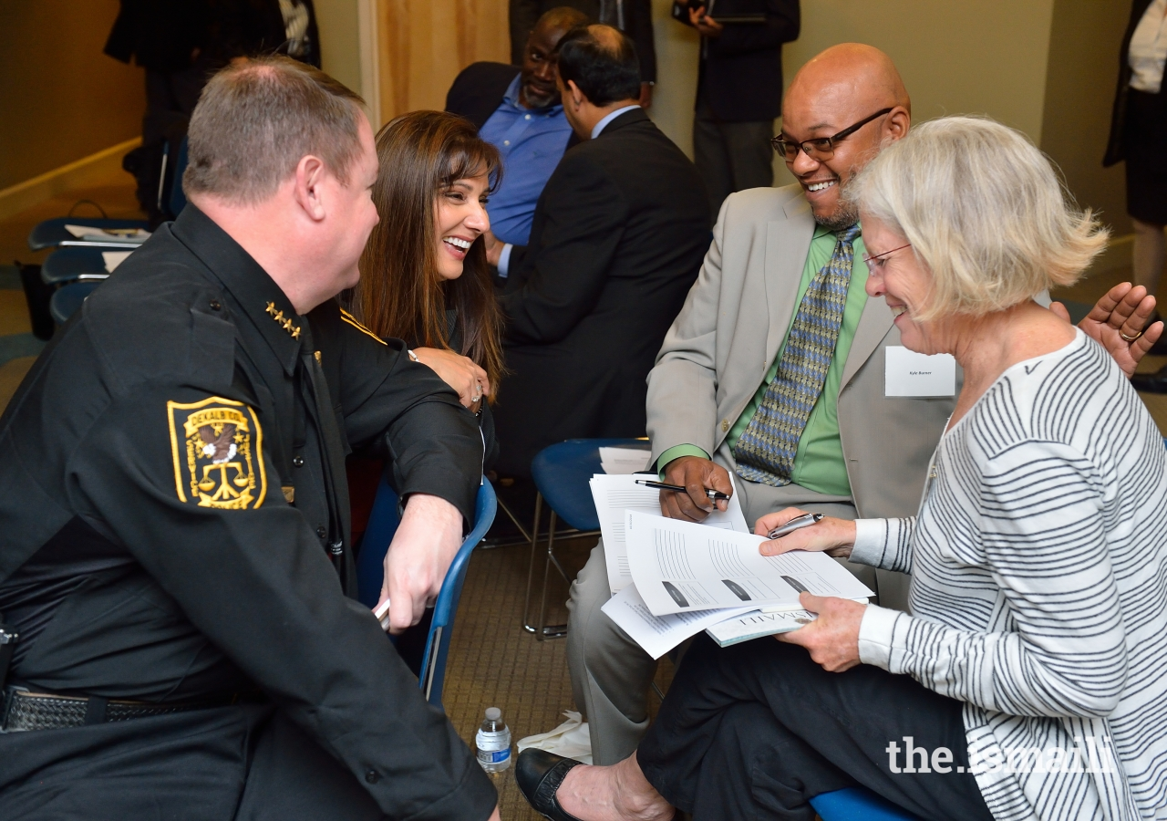 Police officers, clergy, educators, and community peacebuilders discuss implicit bias in group break-out sessions.