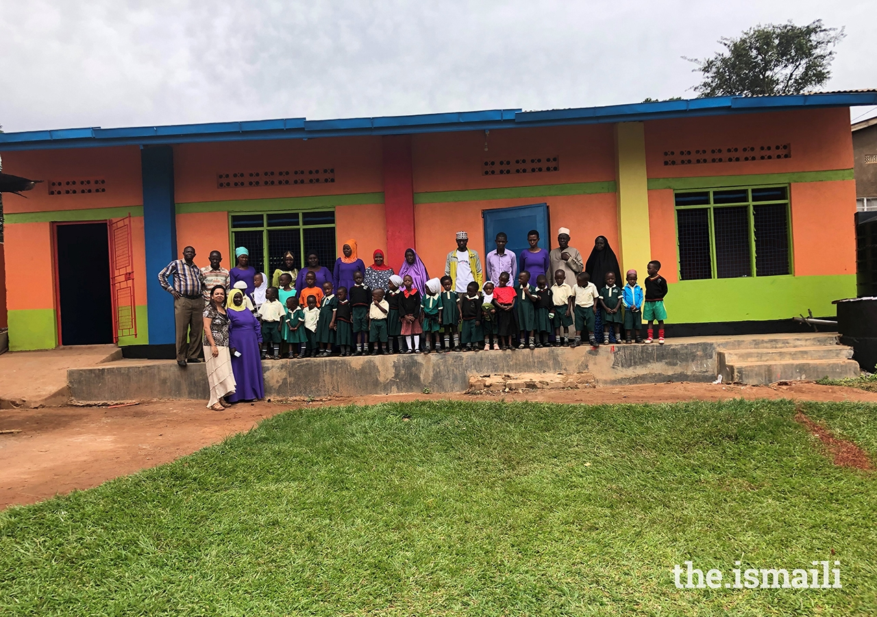 School members pose in front of the newly-painted facade of the school.
