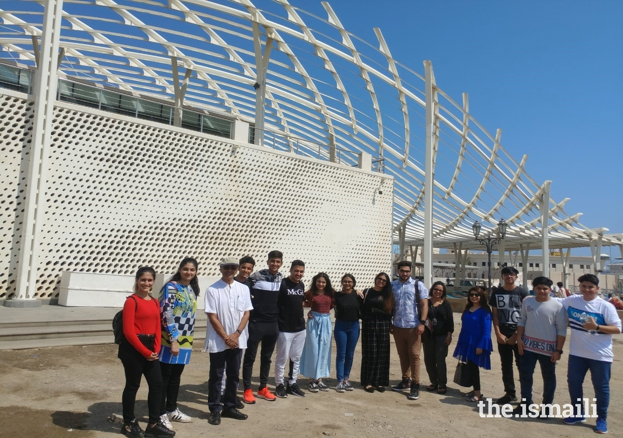 Participants of the international excursion pose for a photo with Raj Isar outside the fish market's canopy: a fin-like shaded structure inspired by Arabic calligraphy and the play of light and shadow.