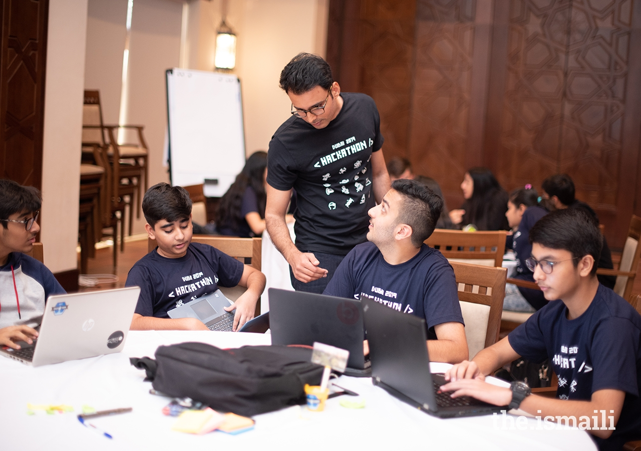 A Hackathon Dubai participant consults with a facilitator to determine if his group is on the right track.