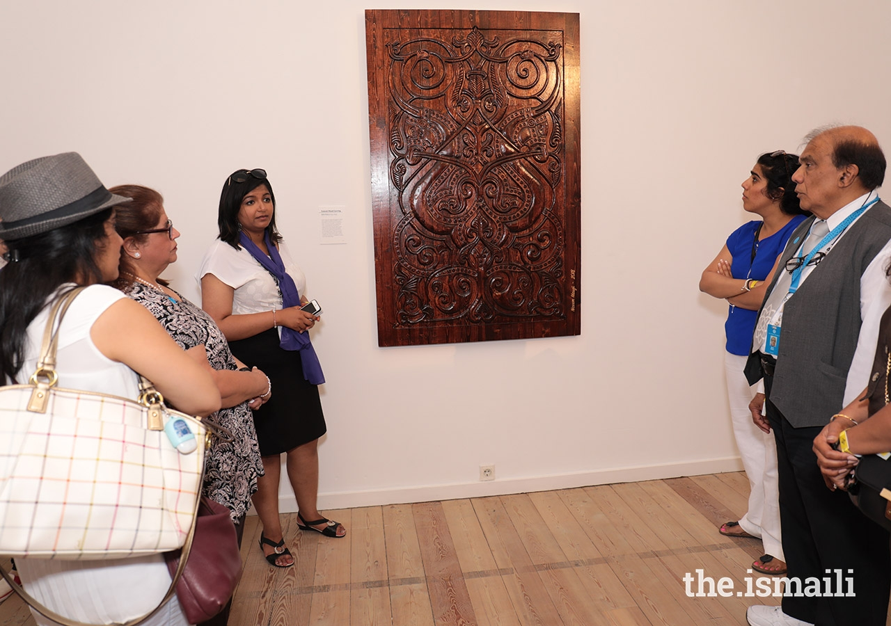Attendees admire a wood carving on display at the International Art Gallery in Lisbon.