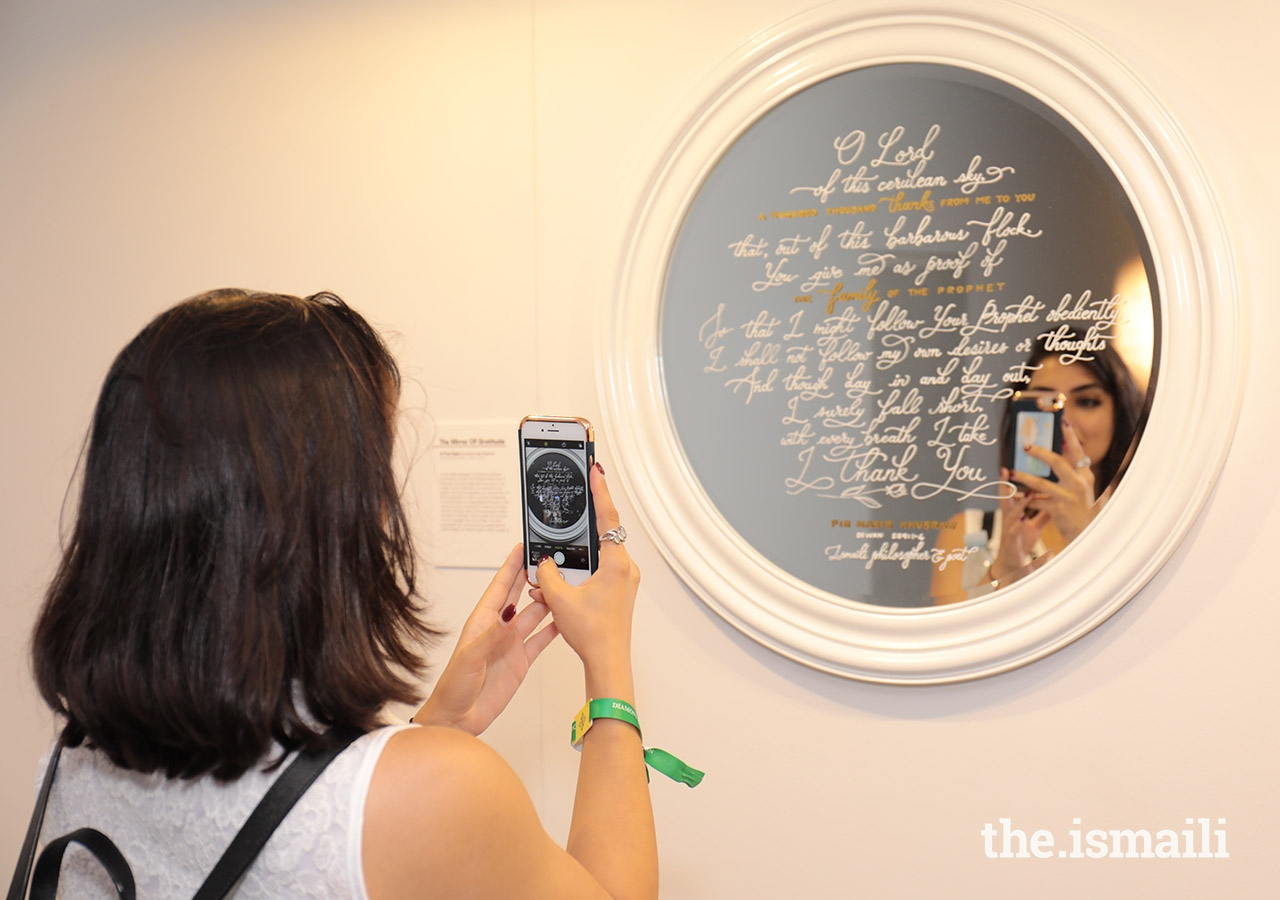 An International Art Gallery attendee snaps a photo of one of the pieces of art on display.