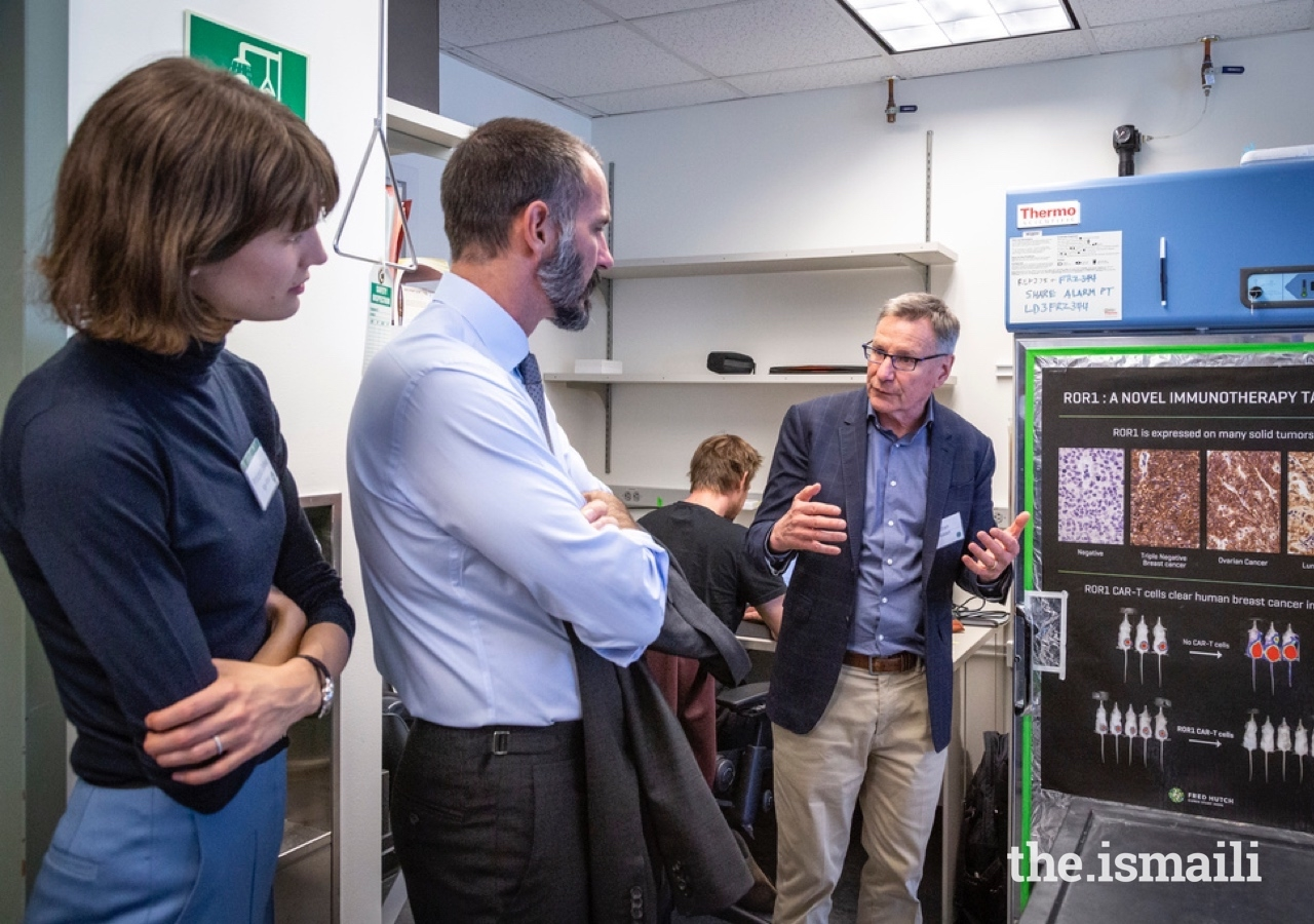 Scientific Director Dr. Stan Riddell in conversation with Prince Rahim and Princess Salwa during a lab tour at Fred Hutchinson Cancer Research Center.