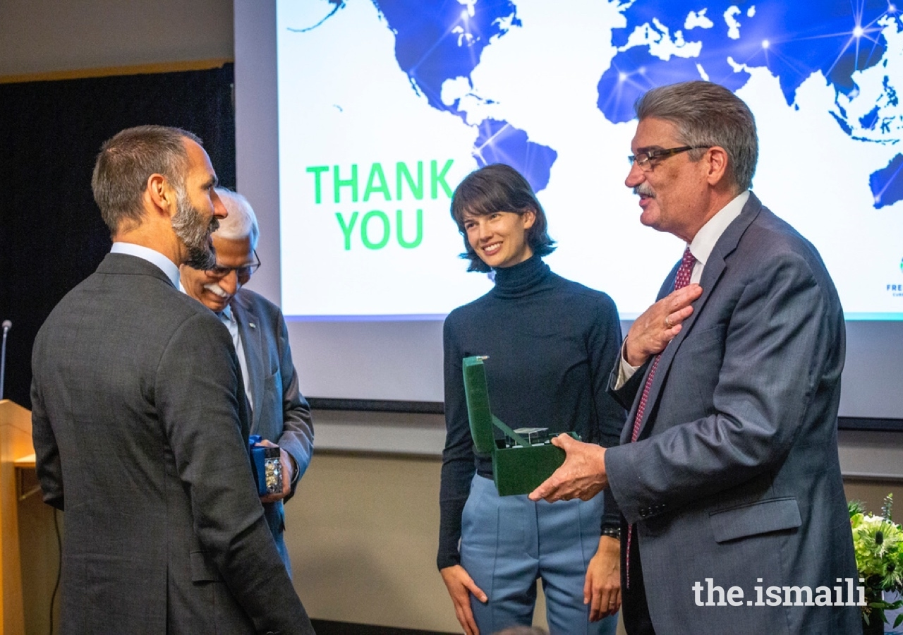 President and Director of Fred Hutch Dr. Gary Gilliland and Prince Rahim exchange gifts after the MOU signing ceremony at the Fred Hutchinson Cancer Research Center as AKU President Firoz Rasul and Princess Salwa look on.