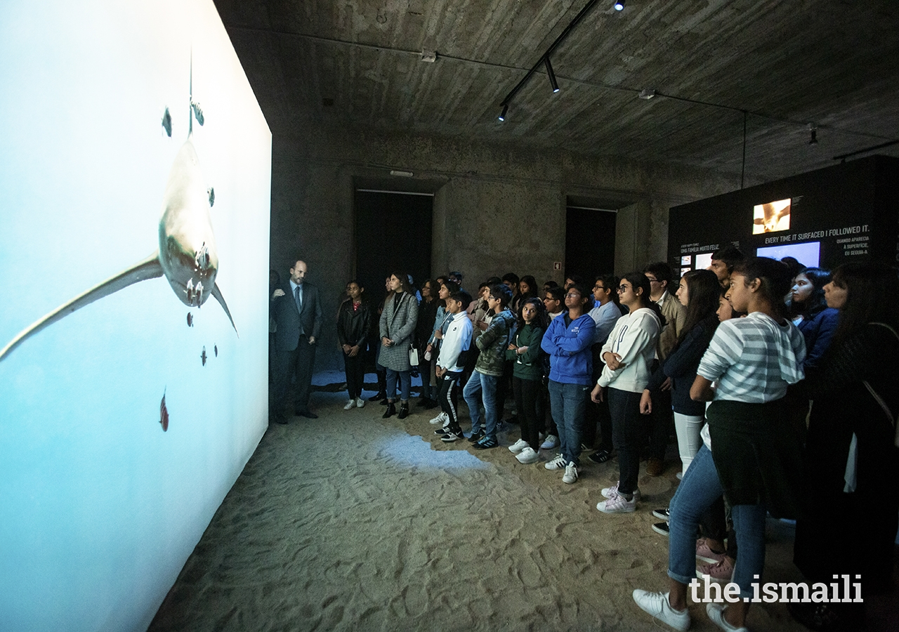 Students listen as Prince Hussain explains the story behind a photo of a shark at The Living Sea photo exhibition in Lisbon.