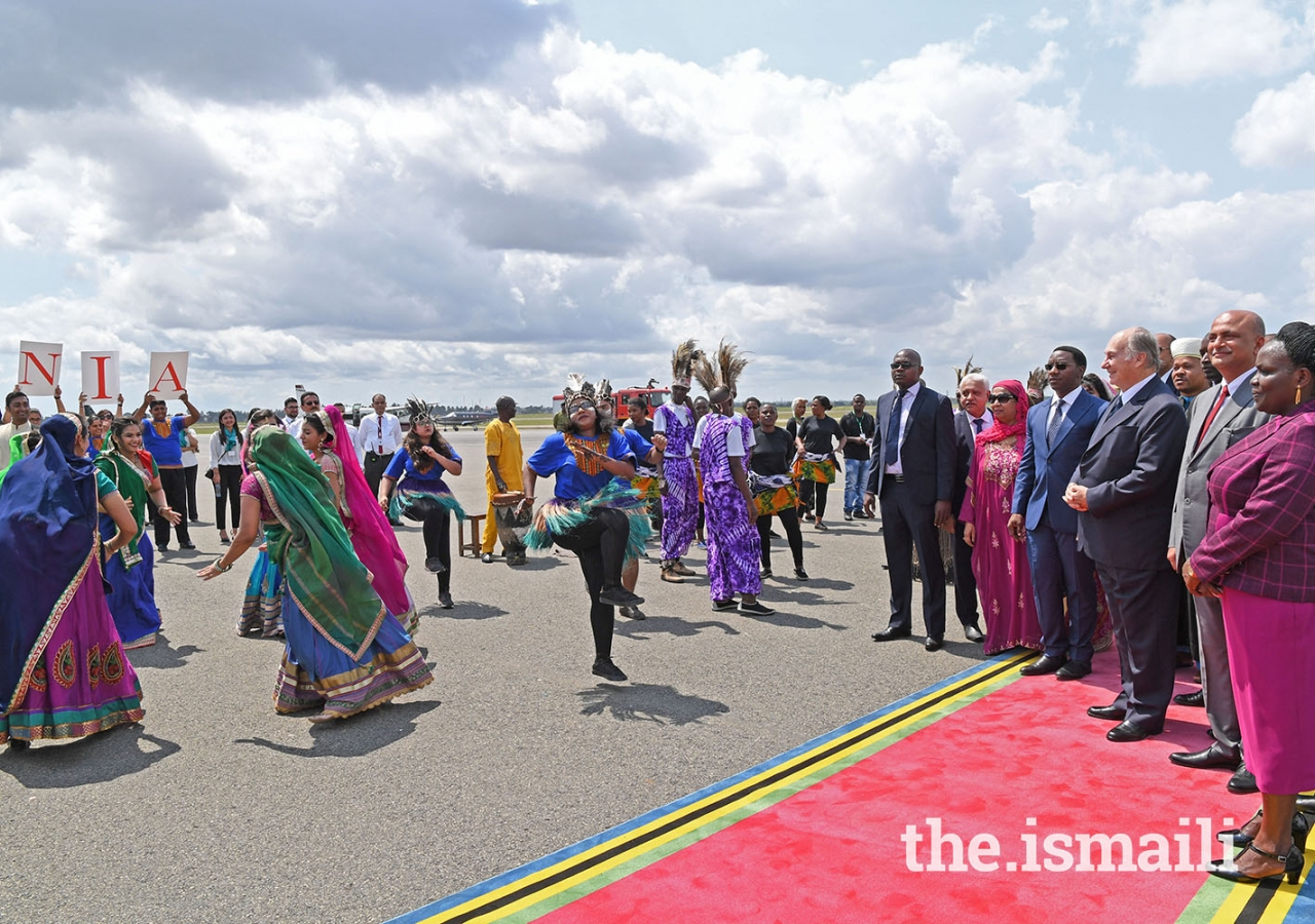"""Mawlana Hazar Imam views a cultural """"Ngoma"""" dance performed by Ismaili Volunteers at the Julius Nyerere Airport."""