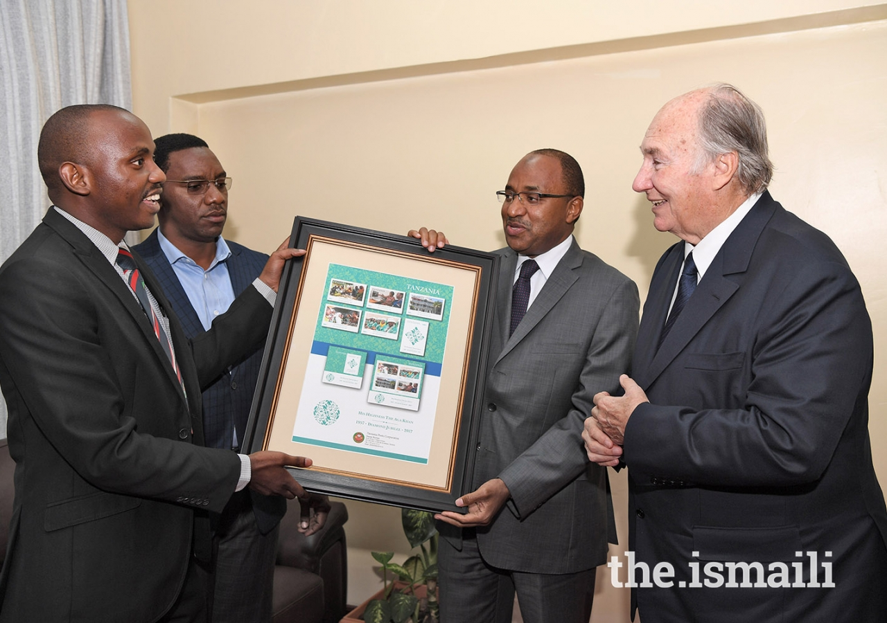 Mawlana Hazar Imam is presented with a gift of First Day Covers and Commemorative Stamps created by the Tanzania Postal Service Corporation in honour of his Diamond Jubilee.