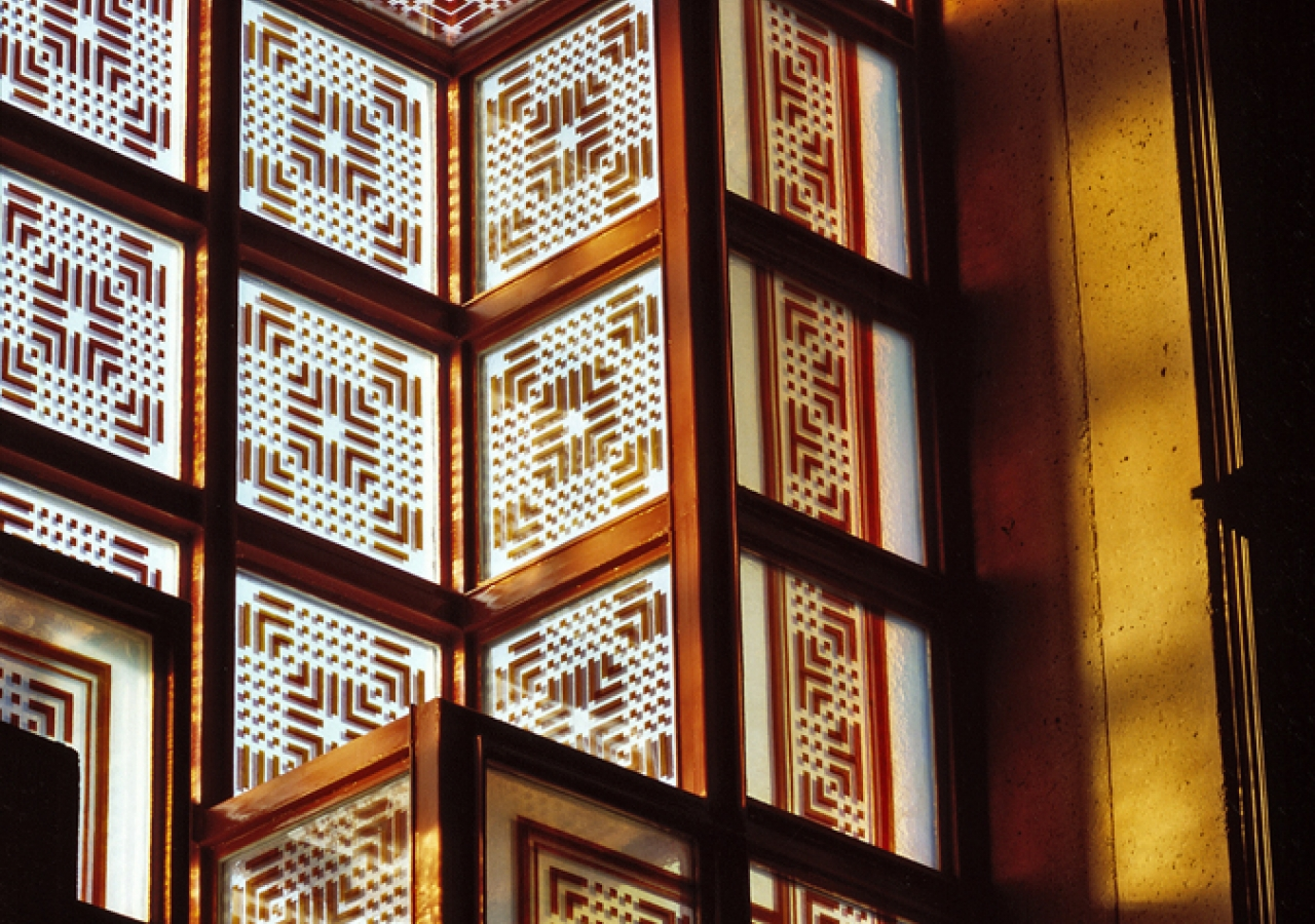 An interior close-up view of the windows, which are decorated with stained geometric patterns.