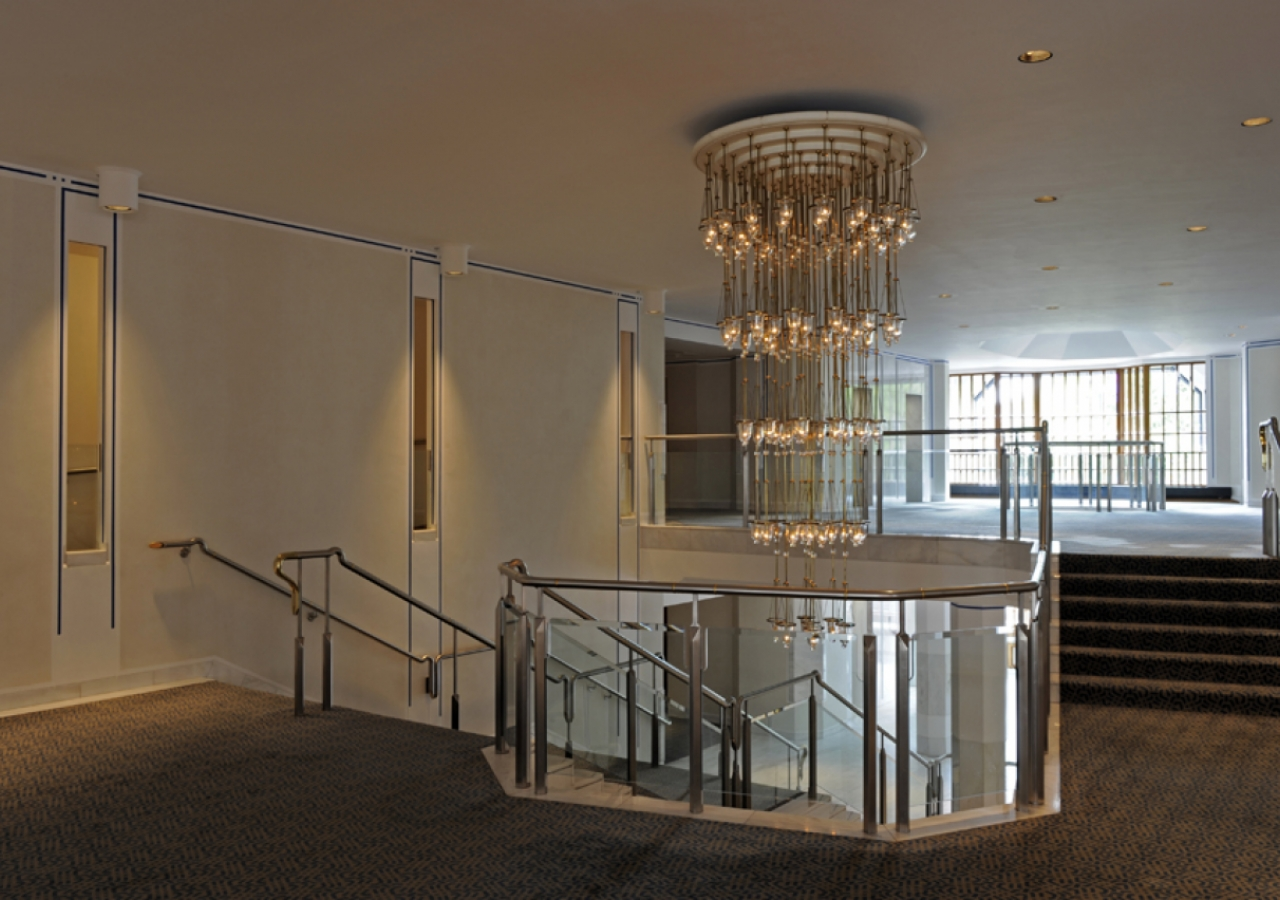 The main stairway pivots about an impressive chandelier.