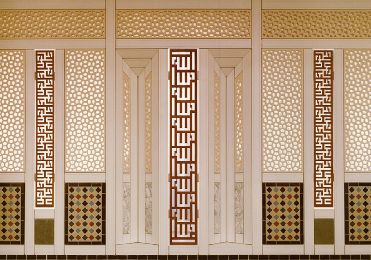 Panelling on the West window wall of the Prayer Hall, designed by Karl Schlamminger, incorporating marble, tile and plaster lattice panels with vertical teak panels in rectangular calligraphy. The names Allah, Muhammad and Ali (not shown) are to be read i