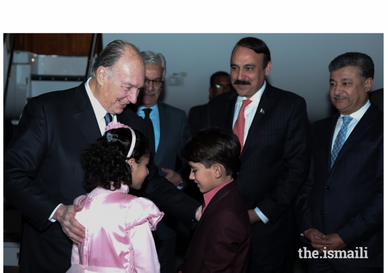 Mawlana Hazar Imam in a light moment with children presenting bouquets