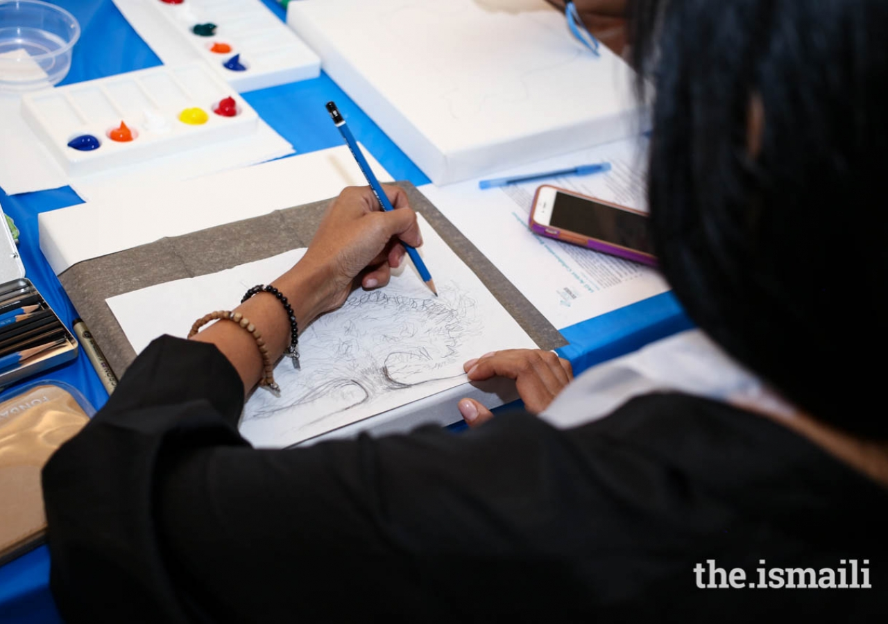 An attendee of the International Art Gallery workshop sketches on canvas.