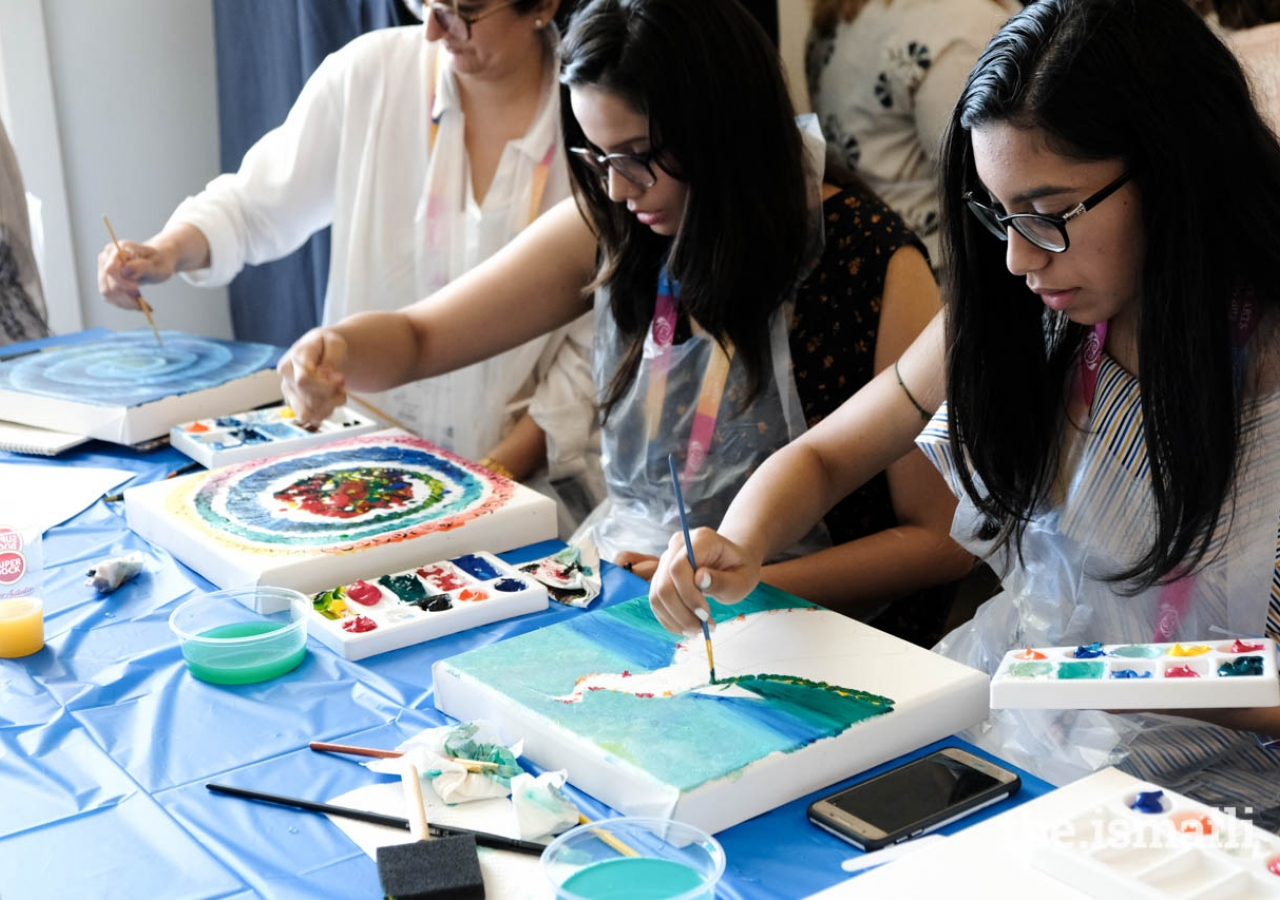 Participants of a workshop hosted by the International Art Gallery paint on canvas at an event promoting doing art together.