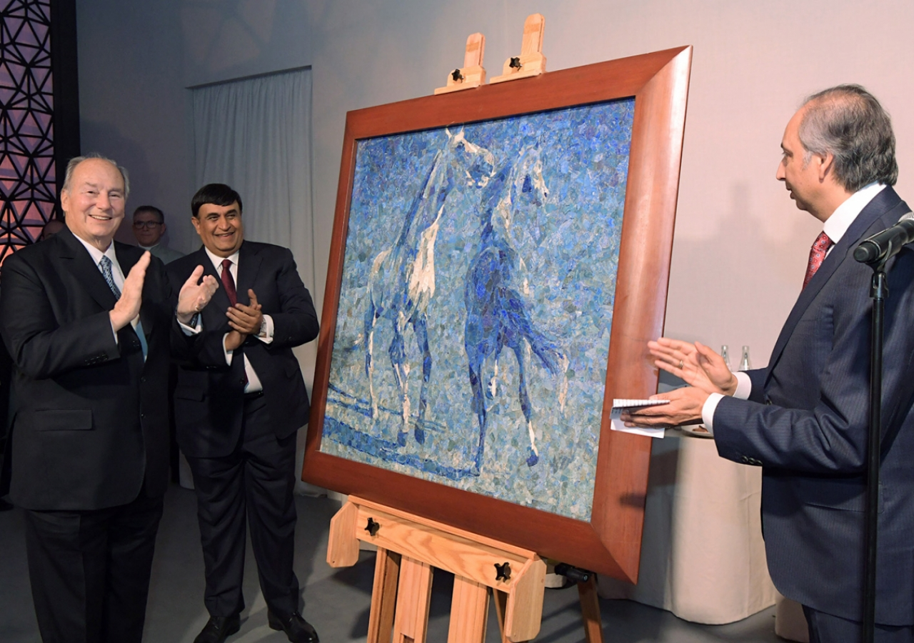 """Mawlana Hazar Imam is presented with a birthday gift on behalf of the global Jamat. Titled """"Horses"""", this lapis lazuli mosaic was commissioned from the late Ismail Gulgee in 1989. Photo: Zahur Ramji"""