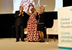 Alice Wairimu Nderitu raises the Global Pluralism Award as Mawlana Hazar Imam and Chief Justice Beverly McLaughlin applaud. Nderitu was recognised for mediating and brokering peace in multiple ethnic conflicts throughout Africa.
