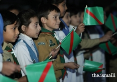 Young scouts and guides waving the national flag, the Ismaili flag and the Diamond Jubilee flag.