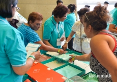 Memorabilia volunteers help Jamati members with finding a Diamond Jubilee shawl.