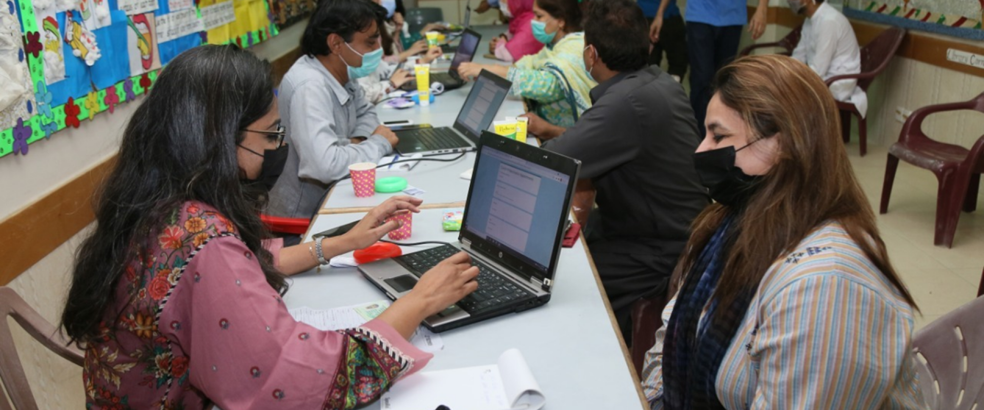 Volunteers collect data from members of the Jamat at the vaccination centre.