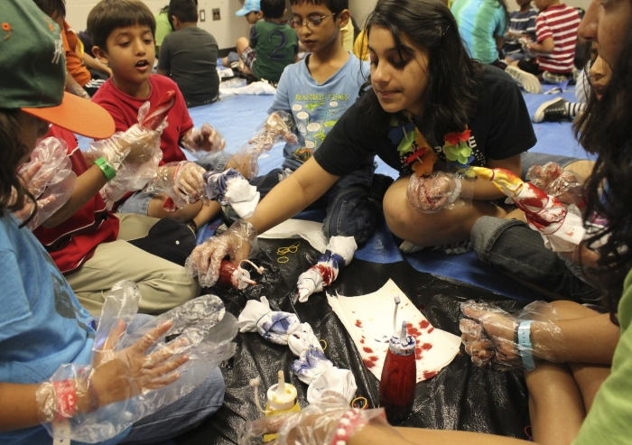 A counselor helps participants tie-die shirts during a self-expression activity at an Ismaili summer camp.