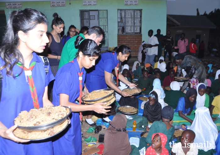 Young members of the Aga Khan Scouts and Guides in Uganda serve meals to orphaned children at the Kasanagati Orphan Fans Society in Kawanda.