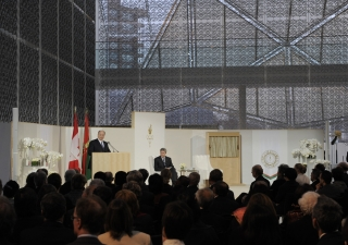 Mawlana Hazar Imam, speaking at the opening ceremony of The Delegation of the Ismaili Imamat, situated on Sussex Drive in Ottawa. Looking on, in the glass-domed atrium adorned with Jali screen is the Right Honourable Stephen Harper, PM of Canada