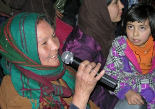 At the Kabul International Women's Day event organised by the Ismaili Council for Afghanistan, an audience member asks a question, as a young girl looks on.