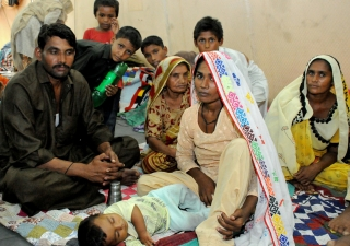 A family finds shelter from the flood devastation at a FOCUS relief camp in Sindh.