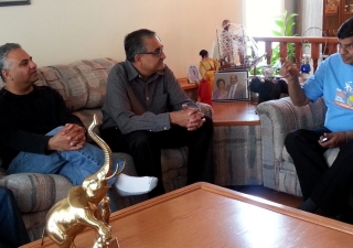 Ismaili Council for Canada President Malik Talib, Honorary Secretary Arif Amlani and President Mohamud Zaver of the Ismaili Council for the Praries visit with a host family and their guest, who was evacuated from a flooded Calgary neighbourhood.