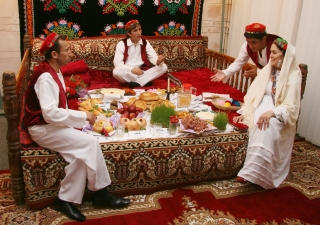 "A family illustrates a traditional Tajik Navroz meal according to the ""haft-shin"" and ""haft-sin"" traditions."