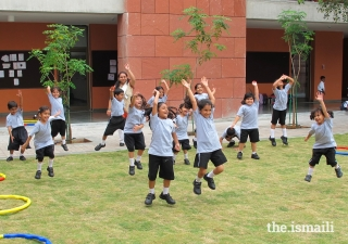 At the Aga Khan Academy in Hyderabad, India, teachers and students enjoy a fun moment of sport together on the campus lawn.